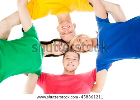 Happy students in colorful clothing standing together hugging.  - stock photo