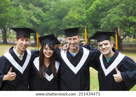 happy students in graduation gowns on university campus - stock photo