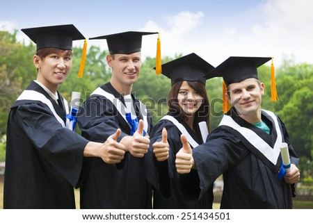 happy students in graduation gowns showing diplomas with thumbs up