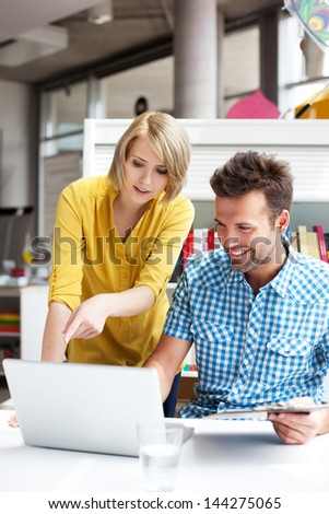 Happy students learning in library on laptop - stock photo