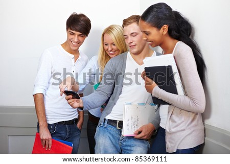 Happy students looking at photos on smartphone