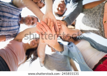 Happy students putting their hands together at the university - stock photo
