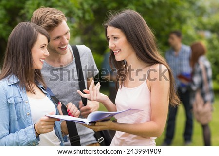 Happy students reading from notepad at the university - stock photo