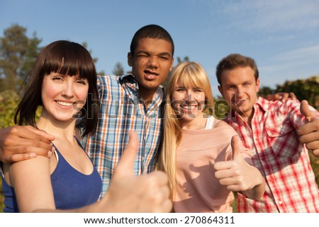 "Happy students show ""Like""gesture in park. Close up shot, focus on faces. - stock photo"