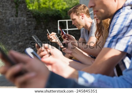 Happy students sitting in a row texting at the university - stock photo