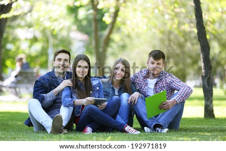 Happy students sitting in park