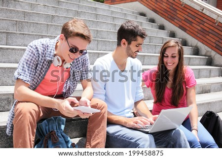 Happy students sitting on stairs using digital tablet and conservation to each other in school, caucasian - stock photo