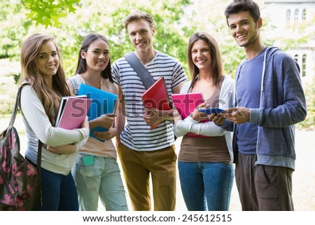 Happy students smiling at camera outside on campus at the university - stock photo
