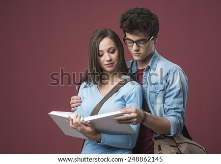 Happy students studying together on an open textbook and smiling - stock photo