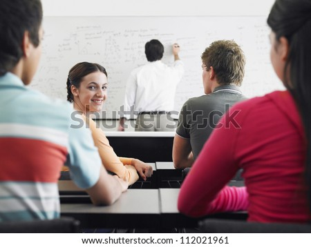 Happy students studying with professor in classroom - stock photo