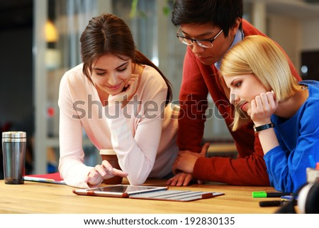 Happy students using tablet computer together - stock photo