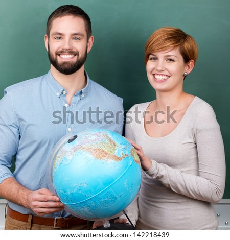 Happy students viewing globe in geography classroom - stock photo