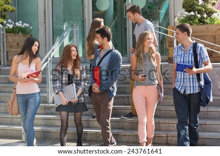 Happy students walking and chatting outside at the university - stock photo