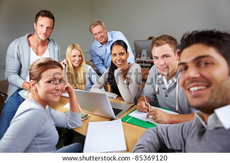 Happy students with teacher in university class - stock photo