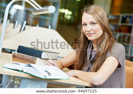 Happy Studying young teenage college student girl in a library with book - stock photo