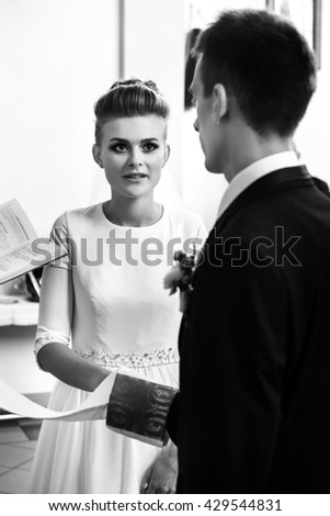 happy stylish bride and elegant groom exchanging vows at catholic wedding ceremony at church - stock photo