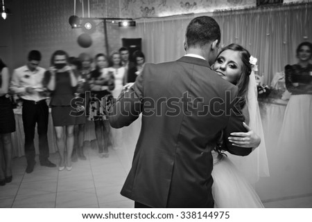 happy stylish brunette bride and groom performing first dance in a restaurant