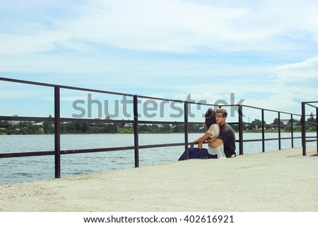 happy stylish couple hugging on pier, relaxing and dreaming in summer vacation, travel together concept