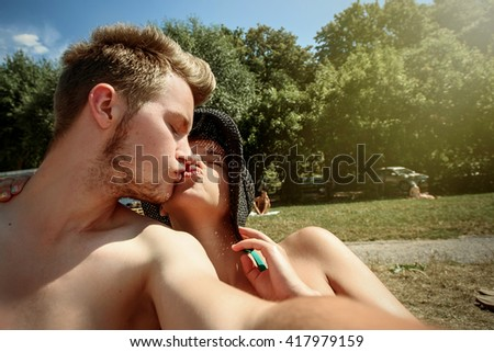 happy stylish couple taking selfie and kissing, having fun on the beach, summer vacation, space for text