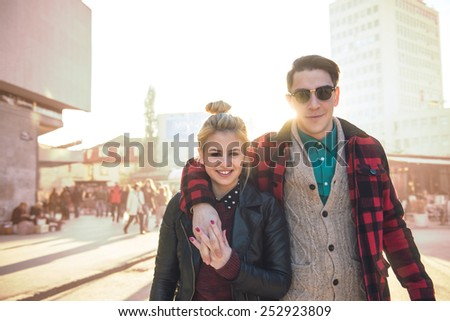 Happy stylish hipster couple walking on the streets. Warm tones, a little bit enhanced on the background. Lens flare added to enhace the sunlight effect - stock photo