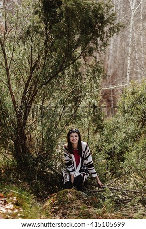 happy stylish hipster woman traveler, sitting in woods in mountains and smiling