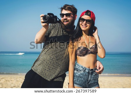 Happy stylish multiracial couple taking a photo with professional camera on a beach on holidays