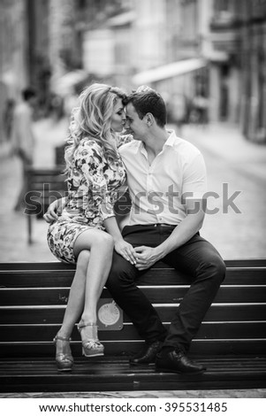 Happy, stylish newlywed couple posing on wooden bench in town b&w