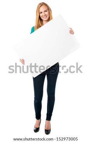 Happy stylish slender young woman holding a blank white sign board or placard at an angle in front of her body, full length on white