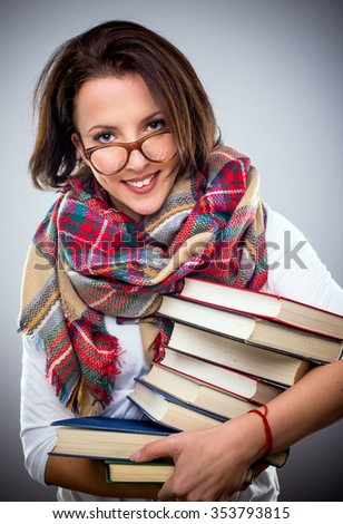 Happy stylish woman in a colorful winter scarf and eyeglasses holding a pile of hardcover books under her arm as she smiles at the camera - stock photo