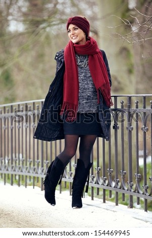Happy stylish woman walking in the cold winter park - stock photo