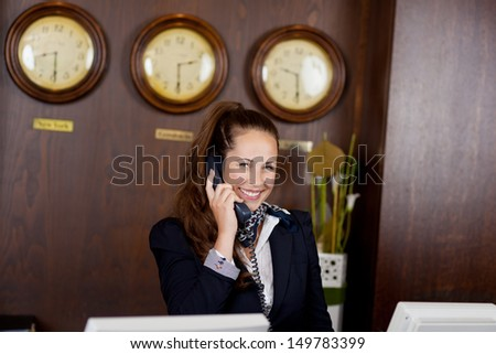 Happy stylish young receptionist talking on a telephone standing behind a counter in a hotel lobby or international venue with time clocks above her head - stock photo