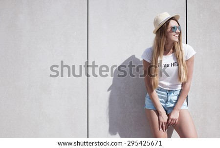 Happy Stylish Young Woman Leaning Against Plain Wall with Copy Space and Looking to the Right of the Frame. - stock photo