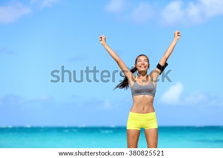 Happy success woman - achievement of fitness goals. Winning female athlete with arms up successful of achieving her workout or diet goal. Healthy Asian runner girl living a healthy lifestyle. - stock photo