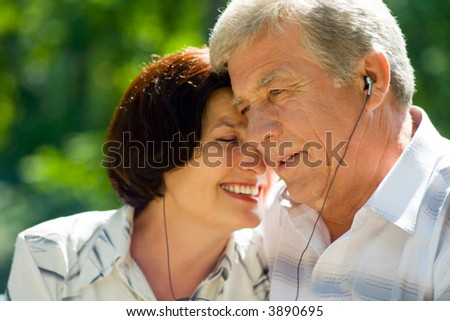Happy successful attractive elderly couple listening music in headset together. Focus on man. - stock photo