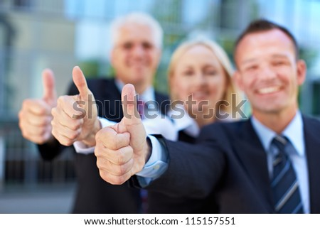 Happy successful business group holding their thumbs up - stock photo