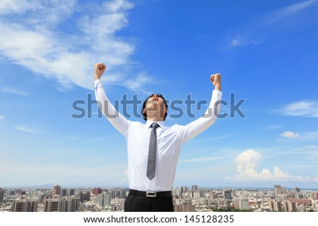 happy successful business man raised arms with cityscape and sky in the background, asian people - stock photo