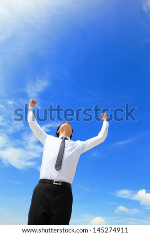 happy successful business man raised arms with sky in the background, asian people - stock photo