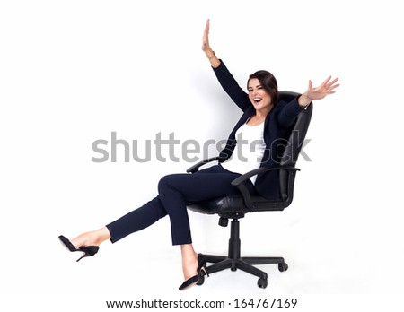 Happy successful business woman in office chair