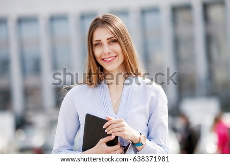 happy successful businesswoman in blue shirt holding touch pad and smiling Manager conducts its business outdoor