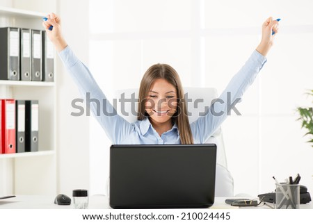 Happy successful Businesswoman in the office with raised arms.