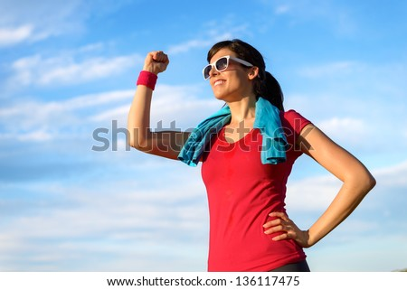 Happy successful fitness woman raising arm with energy and fist to the sky after running and exercising. Sport  goals and achievements concept. Caucasian beautiful female athlete in sportswear. - stock photo
