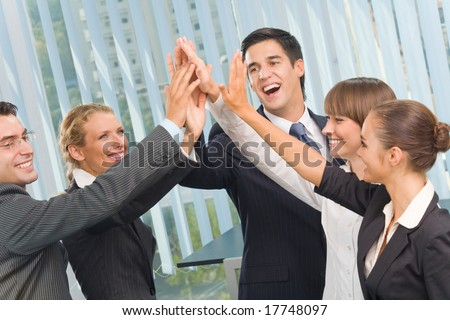 Happy successful gesturing business team at office - stock photo