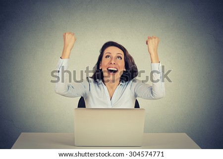 Happy successful girl with arms raised up using a laptop computer - stock photo