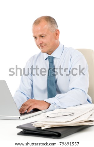 Happy successful mature businessman working in office behind desk isolated