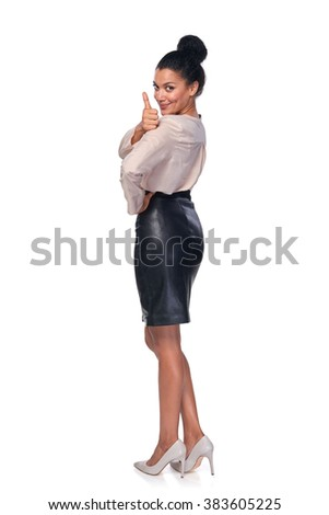 Happy successful mixed race caucasian - african american business woman in full lengh gesturing thumb up sign and smiling at camera