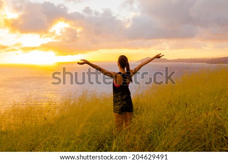 Happy successful sportswoman raising arms to the sky on golden back lighting sunset summer. Fitness athlete with arms up celebrating goals after sport exercising and working out outdoors. Copy space. - stock photo