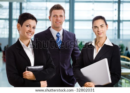 Happy successful young business people standing side by side at office lobby, smiling, looking at camera.