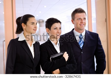 Happy successful young business people standing side by side at office lobby, smiling, looking away. - stock photo