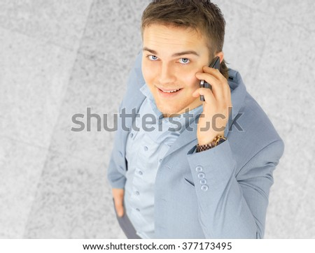 happy successful young businessman talking on mobile phone - stock photo