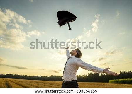 Happy Successful Young Businessman Throwing His Coat in the Air for being Free of Something with Wide Open Arms at the Field During Sunset. - stock photo